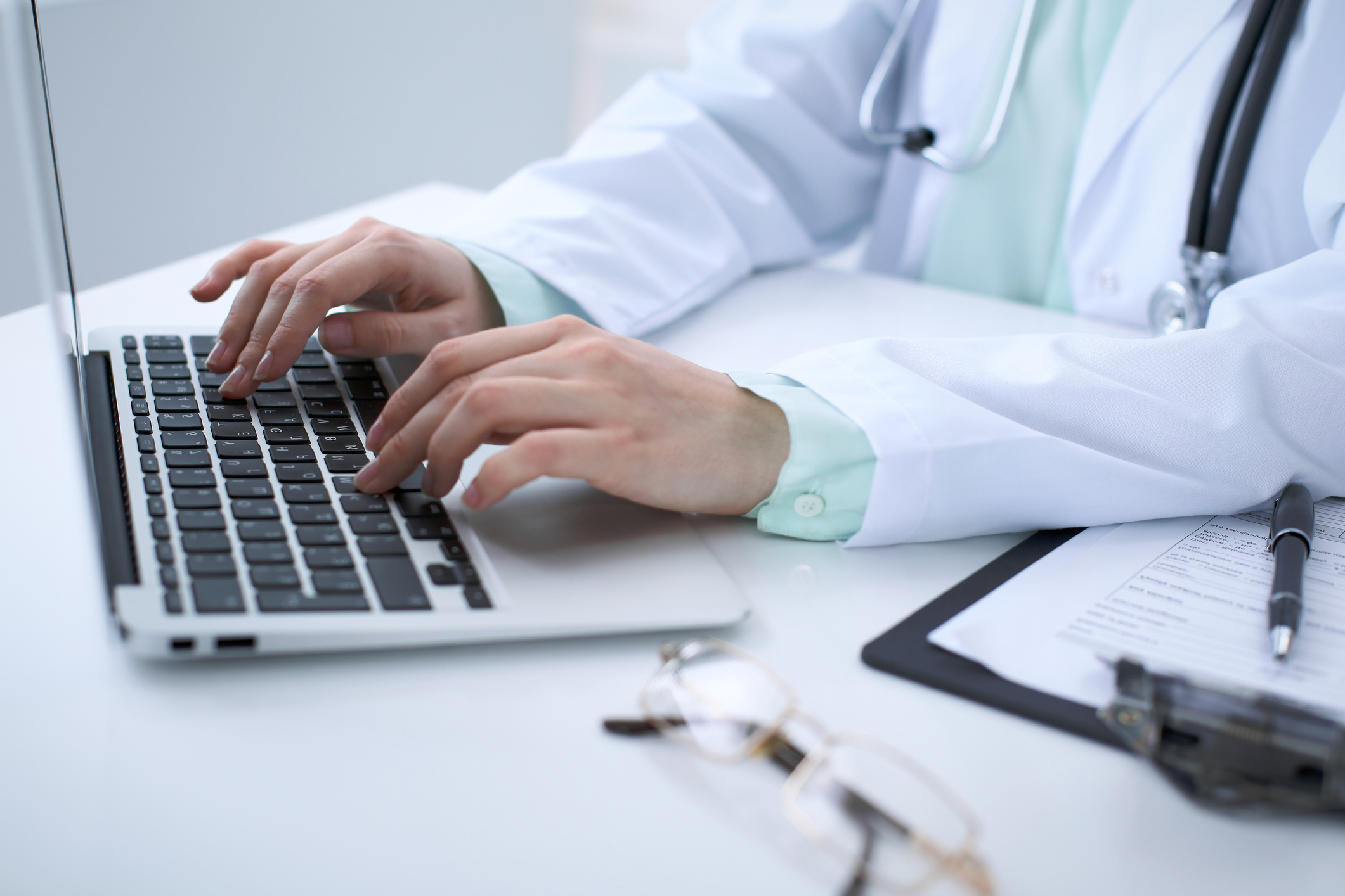 Close-up-of-a-female-doctor-typing-on-laptop-computer,-sitting-at-the-table-in-the-hospital-867698684_2125x1416-1